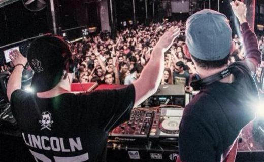 Adam Bartas & Dean Paps of Orkestrated deejaying in a crowded club
